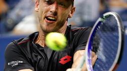 Petenis Australia, John Millman menggembalikan bola pukulan Roger Federer dari Swiss saat bertanding pada babak 16 besar AS Terbuka 2018 di New York, (4/9). Federer kalah dari John Millman 3-6, 7-5, 7-6 (9-7), 7-6 (7-3). (AP Photo/Jason DeCrow)
