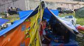 Seorang anak laki-laki mengintip dari tenda ketika orang-orang yang terkena gempa tinggal di kamp sementara setelah gempa berkekuatan 6,2 di Mamuju, Senin (18/1/2021). Ratusan jiwa telah mengungsi di sejumlah posko pengungsian karena rumah mereka rusak akibat gempa. (AFP/Adek Berry)