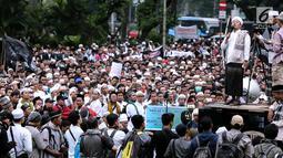Seorang peserta aksi berorasi di depan ribuan massa yang tergabung dalam aliansi ormas dan umat Islam Jabodetabek menggelar aksi unjuk rasa di Pintu Barat Monas, Jakarta, Selasa (18/7). (Liputan6.com/Faizal Fanani)