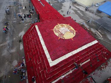 Penduduk setempat menyelesaikan pembuatan piramida Cochasqui dari bunga mawar dalam upaya pemecahan Guinness World Records di Tabacundo, Ekuador, 20 Juli 2018. Piramida dibangun di lahan seluas 1.100 meter tanpa henti oleh para relawan (AP/Dolores Ochoa)
