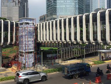 Suasana pembangunan lift pada jembatan penyeberangan orang di kawasan Senayan, Jakarta, Senin (13/5). Pembangunan lift pada tiga JPO yang berada di Jalan Sudirman itu bertujuan meningkatkan kenyamanan kepada warga dan ditargetkan rampung akhir bulan ini. (Liputan6.com/Immanuel Antonius)