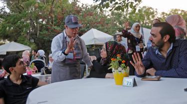 "Seorang anak down syndrome Abdel Rahman melayani pelanggan di kedai kopi Sucet  selama festival ""Sham gather us"" di Damascus (11/7). Enam belas anak laki-laki dan perempuan down syndrome bekerja di Cafe Sucet melayani pelanggan. (AFP Photo/Louai Beshara)"