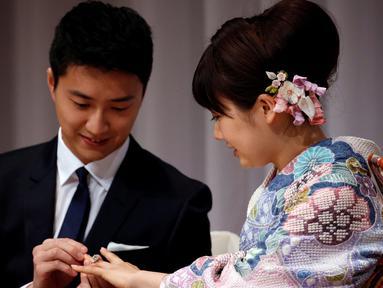 Atlet tenis meja Taiwan, Chiang Hung-chieh memasangkan cincin pernikahan ke tangan atlet tenis meja Jepang, Ai Fukuhara saat mengumumkan pernikahan kepada wartawan pada jumpa pers di Tokyo, Jepang, (21/9). (REUTERS/Toru Hanai)
