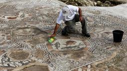 Seorang peneliti sejarah kuno membersihkan sebuah gambar yang ada pada lantai sebuah peradaban pada 1.700 tahun yang lalu di Tel Aviv, Israel, Senin (16/11/2015). Dulunya kota ini merupakan kota yang makmur. (REUTERS/Nir Elias)