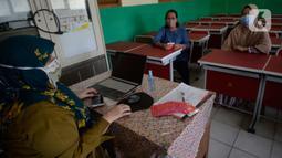 Guru membagikan dua kartu perdana Tri dan Telkomsel beserta kuota gratis kepada wali murid di SDN Serua Indah 1 dan II, Ciputat, Tangerang Selatan, Senin (15/9/2020). Program Kartu Perdana tersebut untuk mendukung kegiatan belajar secara online di masa pandemi covid-19. (merdeka.com/Dwi Narwoko)