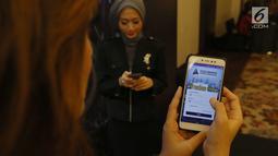 Model menunjukkan aplikasi mobile SIPerdana (System Informasi Peserta Dana Pensiun) PT Asuransi Jiwa Tugu Mandiri usai di luncurkan di Jakarta, Rabu (28/3). (Liputan6.com/Angga Yuniar)