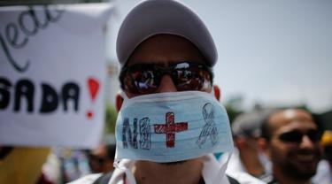 Seorang dokter memakai masker saat unjuk rasa menuntut Presiden Venezuela Nicolas Maduro karena memburuknya ekonomi dan kondisi kemanusiaan di Caracas, Venezuela, (22/5). Sedikitnya 46 orang telah meninggal dunia. (AP Photo/Ariana Cubillos)