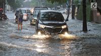 Sejumlah kendaraan menerobos banjir di kawasan Kemang, Jakarta Selatan, Kamis (18/10). Akibat hujan deras, kawasan di Jalan Kemang kembali tergenang air. (Liputan6.com/Herman Zakharia)