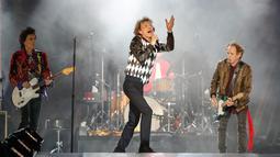 Penampilan Mick Jagger (tengah), Ronnie Wood (kiri), dan Keith Richards saat konser Rolling Stones dalam tur 'No Filter' di Soldier Field, Chicago, AS, Jumat (21/6/2019). Ini konser pertama Rolling Stones dalam tur AS dan Kanada setelah menunda untuk perawatan medis Jagger. (Kamil Krzaczynski/AFP)