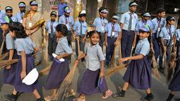 Sejumlah pelajar India membawa sapu saat mengambil bagian dalam 'Swachh Bharat Abhiyan' atau kampanye kebersihan di Hyderabad (12/2). Kampanye ini bertujuan untuk membersihkan jalanan dan infrastruktur di kota-kota India. (AFP Photo/Noah Seelam)