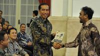 Glen Fredly memberikan DVD film Cahaya dari Timur kepada Presiden Jokowi saat peringatan Hari Film Nasional ke-65 di Istana Negara, Jakarta, Senin (30/3/2015). (Liputan6.com/Faizal Fanani)