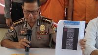 Kabid Humas Polda Kepri, Kombes Erlangga menunjukkan barang bukti iklan perekrutan tenaga kerja yang ternyata bohong. (foto: Liputan6.com / ajang nurdin)