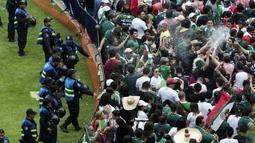 Fans Meksiko melepaskan semprotan busa saat merayakan kemenangan timnya atas Jerman pada laga grup F Piala Dunia 2018 di Monumen Angel of Independence,  Meksiko City (17/6/2018). Meksiko menang 1-0. (AP/Anthony Vazquez)