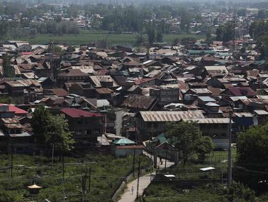 Seorang pria berjalan di jalan yang sepi selama penguncian di Srinagar, Kashmir yang dikuasai India (8/5/2020). Para ulama dan otoritas agama di bagian Kashmir India telah mendesak orang-orang untuk beribadah di dalam rumah mereka untuk mencegah penyebaran Covid-19 . (AP Photo/Mukhtar Khan)