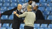 Pelatih Real Madrid Zinedine Zidane berjabat tangan dengan Manajer Manchester City Pep Guardiola usai laga leg kedua babak 16 besar Liga Champions di Etihad Stadium, Sabtu (8/8/2020) dini hari WIB.(Peter Powell / Foto Pool via AP)