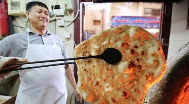 Tukang roti memanggang roti Iran atau taftoon di sebuah toko di Kuwait City, Kuwait, 27 Juni 2019. Taftoon telah menjadi makanan pokok di Kuwait selama beberapa dekade. (YASSER AL-ZAYYAT/AFP)