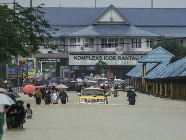 Warga menerobos banjir yang menggenangi jalanan di depan Kantor imigrasi dan bea cukai di Rantau Panjang, Selasa (3/1). Akibat hujan lebat yang turun terus menerus selama empat hari di Malaysia, 5000 warga terpaksa dievakuasi. (AFP PHOTO/STR/Malaysia OUT)