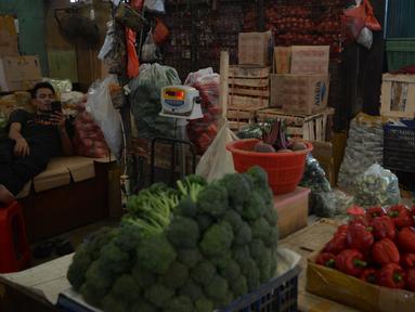 Seorang pedagang melihat ponselnya saat menunggu pembeli di di pasar Induk Kramat Jati, Jakarta, Rabu (7/4/2021).  Semua bahan pangan seperti cabai dan bawang akan stabil jelang puasa Ramadan dan Lebaran Idul Fitri 2021. (merdeka.com/Imam Buhori)