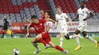 Striker Bayern Munchen, Robert Lewandowski, berebut bola dengan pemain Eintracht Frankfurt, David Abraham, pada laga Piala Jerman di Allianz Arena, Rabu (10/6/2020). Bayern Munchen menang 2-1 atas Eintracht Frankfurt. (AP/Kai Pfaffenbach)