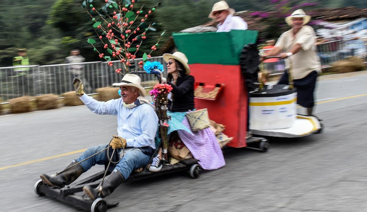 Para peserta menuruni bukit menggunakan kendaraan buatan mereka sendiri dalam festival kendaraan luncur dengan nama Car Festival di Medellin, Kolombia, 17 November 2019. Car Festival ke-30 ini menggunakan gerobak buatan yang dibuat mirip seperti mobil. (JOAQUIN SARMIENTO/AFP)