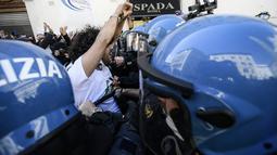 Pengunjuk rasa menghadapi polisi anti huru-hara saat aksi protes pemilik restoran dan aktivitas bisnis lainnya di luar parlemen di Piazza Montecitorio di Roma, Selasa (6/4/202). Mereka memprotes penutupan bisnis dan tindakan pembatasan untuk mengatasi lonjakan COVID-19. (Filippo MONTEFORTE/AFP)