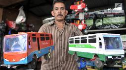 Sukma menunjukkan mainan kayu yang dijualnya di kawasan Kalibata, Jakarta, Rabu (17/10). Sukma menjual jenis mainan tradisional seperti miniatur bus, kereta, bajaj, kuda-kudaan, dan hiasan rumah. (Merdeka.com/Iqbal S. Nugroho)