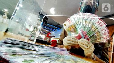 Teller menunjukkan uang tunai pecahan Rp75 ribu di Kantor Cabang Bank BTN Jakarta Harmoni, di Jakarta. Bank BTN mengalokasikan likuiditas dana senilai Rp13,4 triliun untuk memenuhi kebutuhan uang tunai nasabah perseroan pada Idul Fitri 1442 H selama 10 hari mulai 8-17 Mei. (Liputan6.com/HO/BTN)