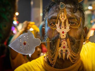 Umat Hindu menusuk pipinya dengan batang logam saat Festival Thaipusam di Batu Caves, Kuala Lumpur, Malaysia, Sabtu (8/2/2020). Acara tahunan ini digelar untuk menghormati Dewa Murugan, mencari berkah, memenuhi sumpah, dan mengucapkan terima kasih. (AP Photo/Vincent Thian)