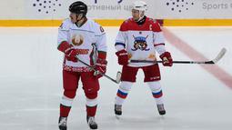 Presiden Rusia Vladimir Putin (kanan) dan Presiden Belarus Alexander Lukashenko (kiri) ikut serta dalam pertandingan hoki es di Shayba Arena, Resor Laut Hitam Sochi, Rusia, (15/2). (Sergei Chirikov / Pool / AFP)