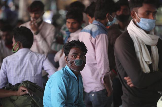 Buruh migran yang memakai masker sebagai antisipasi terhadap virus corona menunggu pengangkutan di terminal bus di Jammu, India(26/3/2021). Pihak berwenang di kota Mumbai mengatakan mereka akan menggelar tes virus korona acak wajib di tempat-tempat ramai. (AP Photo/Channi Anand)