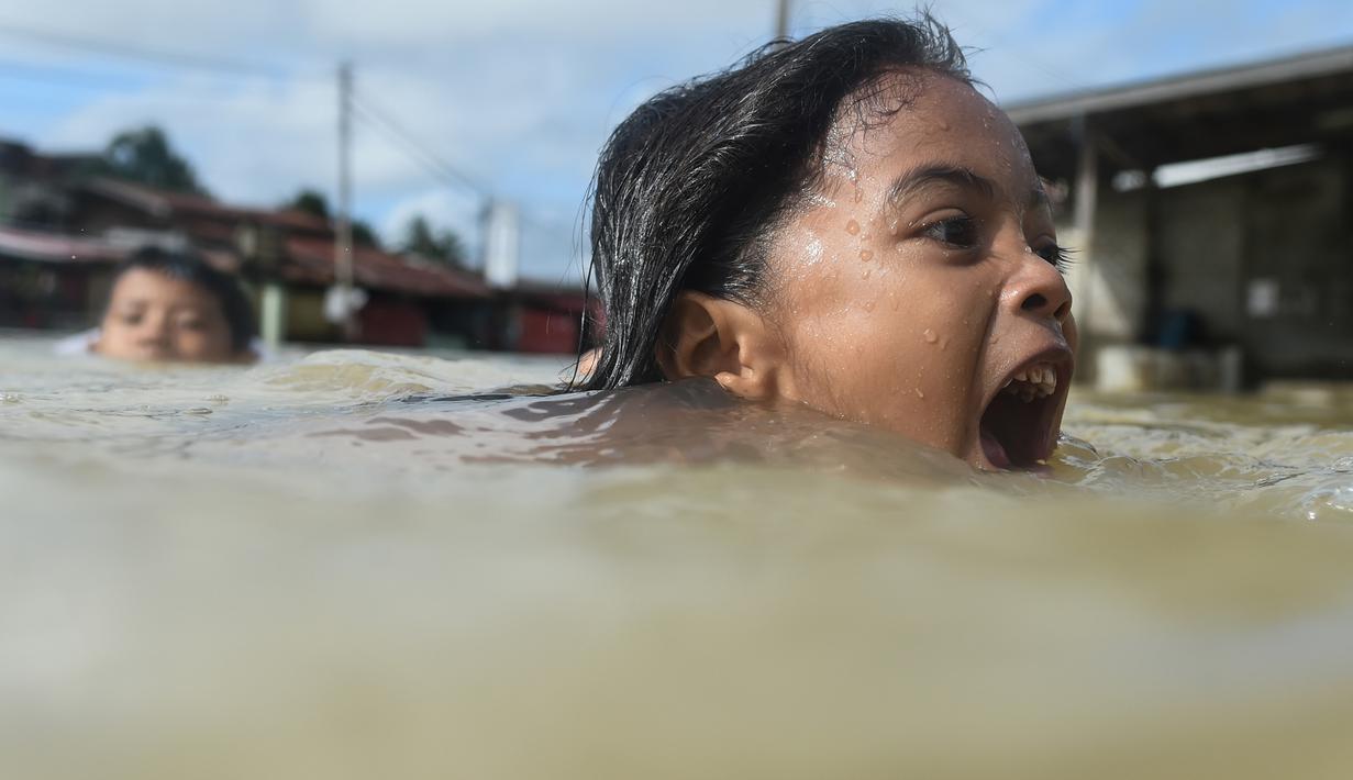 Anak-anak berenang saat banjir melanda kawasan Rantau Panjang, Malaysia, Kamis (5/1). Sekitar 23 ribu orang terpaksa mengungsi karena banjir yang disebabkan hujan muson ini. (AFP PHOTO / MOHD RASFAN)
