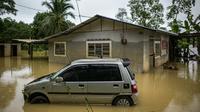 Sebuah mobil terendam banjir di Sementeh, dekat Lanchang di negara bagian Pahang Malaysia (6/1/2021). Hujan deras terus melanda sebagian wilayah Malaysia, menyebabkan ribuan orang dievakuasi di negara bagian selatan Johor dan beberapa bagian jalan raya Pantai Timur di Pahang. (AFP/Mohd Rasfan)