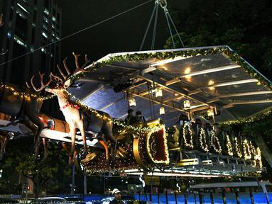 Restoran gantung dengan dekorasi kereta salju santa claus di Kuala Lumpur, Malaysia, Rabu (5/12). Restoran gantung ini menawarkan sensasi menjadi santa claus kepada pengunjung. (MOHD RASFAN/AFP)