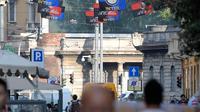 Warga melintas di bawah bendera klub Inter Milan dan AC Milan yang tergantung di jalan Paolo Sarpi, sebuah lingkungan China di Milan, Italia (13/10). Saat ini kedua tim tersebut merupakan milik pengusaha asal China. (AFP Photo/Miguel Medina)