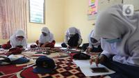 Murid-murid SD dan SMP belajar dengan memanfaatkan wifi gratis di Balai RW kawasan Tegal Gundil, Bogor, Jawa Barat, Senin (21/9/2020). Pemkot Bogor menyebar lebih dari 50 titik wifi publik gratis untuk menunjang Pembelajaran Jarak Jauh (PJJ) siswa di Kota Bogor. (merdeka.com/Arie Basuki)