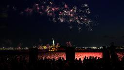 Kembang api meledak di atas Pelabuhan New York dan Patung Liberty di New York, Selasa (15/6/2021). New York menandai berakhirnya pembatasan COVID-19 dengan perayaan kembang api di seluruh negara bagian untuk menghormati para kelompok pekerja penting. (AP Photo/Craig Ruttle)