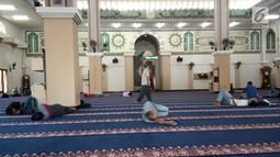 Seorang pria melintas di antara jemaah yang sedang tidur-tiduran di Masjid Agung Baiturrahim, Provinsi Gorontalo, Sabtu (11/5/2019). Sebagian umat muslim menghabiskan waktu dengan tidur di masjid atau melakukan tadarus Alquran pada siang hari selama bulan Ramadan. (Liputan6.com/Arfandi Ibrahim)