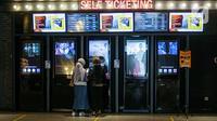 Pengunjung memilih tiket film yang akan ditonton di bioskop CGV Grand Indonesia, Jakarta, Kamis (16/9/2021). Pemerintah memberikan kelonggaran dengan memperbolehkan bioskop buka kembali di wilayah berstatus pemberlakuan pembatasan kegiatan masyarakat (PPKM) level 3 dan 2 (Liputan6.com/Faizal Fanani)
