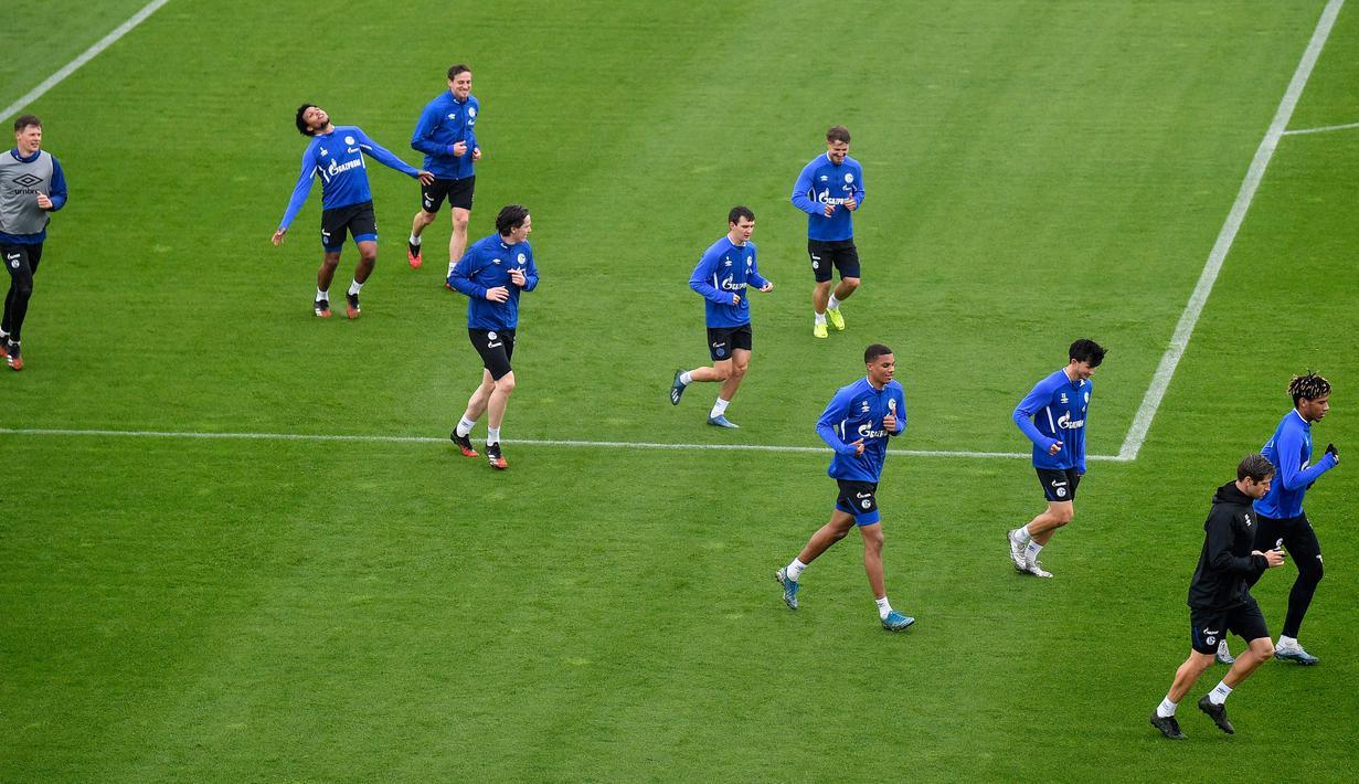 Pemain FC Schalke 04 melakukan pemanasan selama sesi pelatihan di Gelsenkirchen, Jerman, Rabu, (29/4/2020). Meski ada larangan pertemuan besar hingga Agustus untuk melawan pandemi Covid-19, para pejabat sepakbola berharap untuk memulai kembali liga tanpa penonton di bulan Mei. (AP/Martin Meissner)