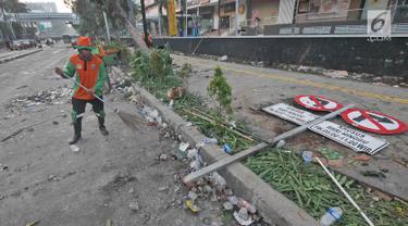 Petugas Penanganan Prasarana dan Sarana Umum (PPSU) atau Pasukan Oranye membersihkan sisa puing-puing pasca kerusuhan di kawasan Wahid Hasyim, Jakarta, Kamis (23/5/2019). Kerusuhan massa yang sebelumnya berdemo di depan gedung Bawaslu melebar ke Jalan Wahid Hasyim. (Liputan6.com/Herman Zakharia)