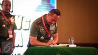 KSAD Jenderal TNI Mulyono saat membubuhkan tanda tangan buku fotografi, Pengabdian Prajurit Kartika di Balai Kartini, Jakarta, Rabu (10/8). (Liputan6.com/Faizal Fanani)