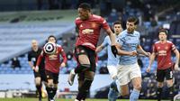 Penyerang Manchester United atau MU Anthony Martial mengontrol bola di samping pemain Manchester City Ruben Dias dalam laga Liga Inggris di Etihad Stadium, Minggu (7/3/2021). (Peter Powell/Pool via AP)