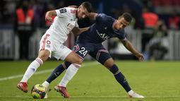 Gelandang Olympique Lyon Houssem Aouar dan bek Paris Saint-Germain (PSG), Thilo Kehrer berebut bola dalam laga pekan keenam Liga Prancis di Stadion Parc des Princes, Senin (20/9/2021) dini hari WIB. PSG menang dengan skor tipis 2-1. (AP Photo/Francois Mori)