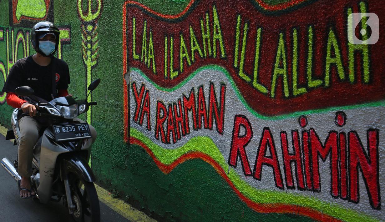 Pengendara melintasi mural bernuansa Islami di Gang Pelangi, kawasan Kalibata, Jakarta, Jumat (23/4/2021). Mural bernuansa Islami tersebut dibuat warga untuk menghiasi dan meramaikan pintu masuk gang dalam rangka menyambut bulan Ramadhan. (Liputan6.com/Herman Zakharia)