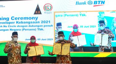 Direktur Utama BTN Haru Koesmahargyo (kanan) bersama pengasuh pondok pesantren Tebuireng KH Abdul Hakim Mahfudz (kiri) mengangkat naskah kerjasama pelatihan santri developer kebangsaan di Jombang, Jawa Timur, Sabtu (05/6/2021). (Liputan6.com/HO/BTN)