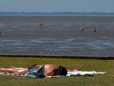 Seorang pria berjemur saat suhu mencapai 34 derajat Celcius di dekat pantai Laut Utara di Wremen, Jerman barat (24/7/2019). Peramal cuaca memprediksi suhu tertinggi di seluruh Eropa barat yang terkena gelombang panas akan mencetak rekor suhu terbaru.  (AFP Photo/Patrik Stollarz)