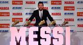 Megabintang Barcelona, Lionel Messi berpose dengan Sepatu Emas Eropa 2018 dan empat trofi lainnya dalam acara di Antiga Fabrica Estrella Damm, Selasa (18/12). Messi berhak atas penghargaan itu setelah mengumpulkan gol terbanyak musim lalu (LLUIS GENE/AFP)