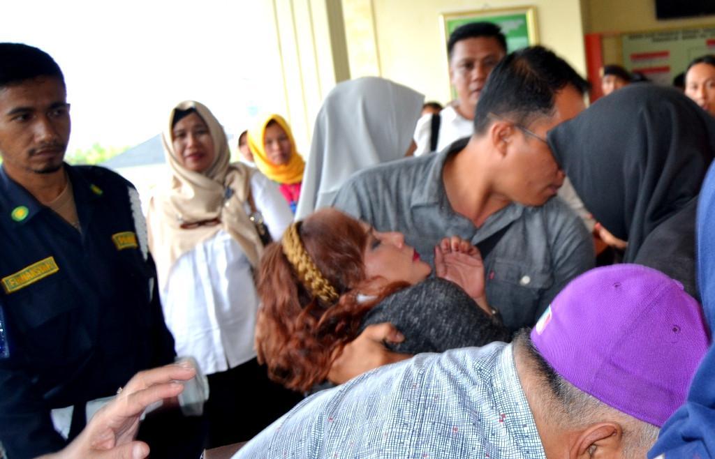 Salah seorang pengunjung sidang terlihat pingsan di luar ruang sidang (Liputan6.com/Yuliardi Hardjo)