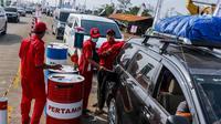Petugas mengisi bahan bakar minyak (BBM) kendaraan di kios Pertamina tol fungsional (tol darurat) Brebes Timur-Gringsing, Tegal, Jawa Tengah, Jumat (30/6). PT Pertamina menjamin ketersedian BBM untuk arus balik aman. (Liputan6.com/Faizal Fanani)