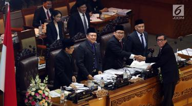 Menkumham Yasonna Laolly menyerahkan pandangan akhir pemerintah soal RUU MD3 kepada Wakil Ketua DPR Fadli Zon saat Rapat Paripurna Pengesahan RUU MD3 menjadi UU, Jakarta, Senin (12/2).  (Liputan6.com/Johan Tallo)